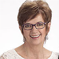 Woman with short brown hair and glasses smiling